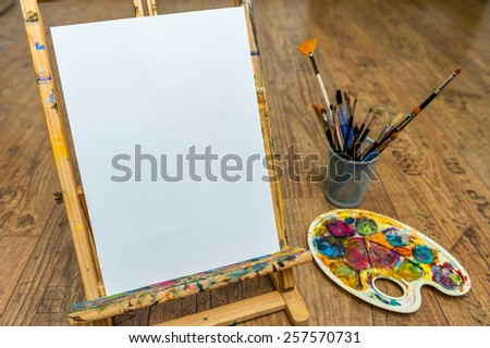 easel palette and brushes with empty white canvas - stock photo