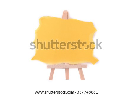 Easel with blank yellow paper in isolated and selective focus