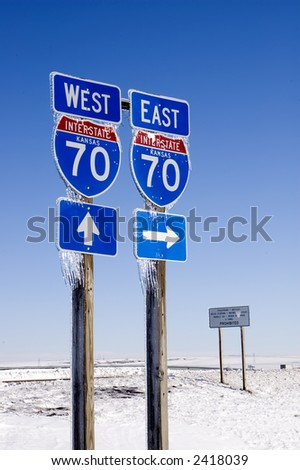 East and west interstate 70 signs with directional arrow signs on wooden posts with icicles and blue sky background - stock photo