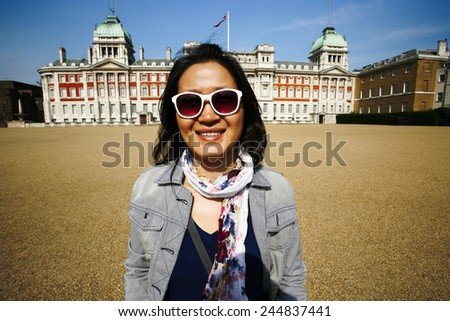 East Asian woman tourist visiting London having fun on a sunny day at Horse Guards Parade ground  - stock photo