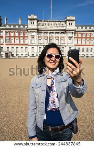 East Asian woman tourist visiting London taking self portrait on a sunny day at Horse Guards Parade ground  - stock photo