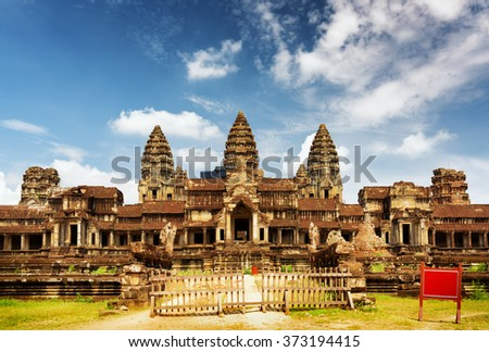 East facade of ancient temple complex Angkor Wat in Siem Reap, Cambodia. Blue sky with clouds in background. Angkor Wat is a popular tourist attraction. - stock photo
