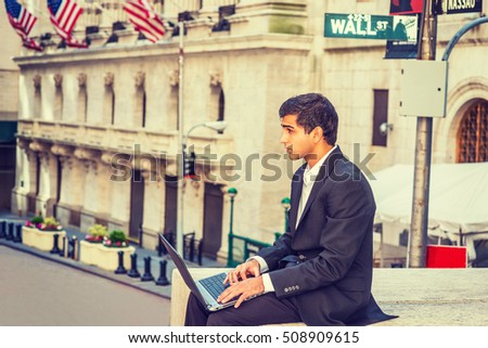 East Indian American Business Man travels, works in New York. Wearing black suit, college student sits on Wall Street by vintage office building with flags, works on laptop computer. Filtered effect.