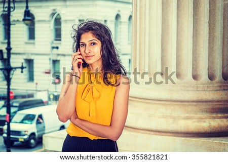 East Indian American Business Woman working in New York. Wearing sleeveless orange shirt, a college student calling on cell phone on street, many cars on background. Instagram filtered effect.  - stock photo