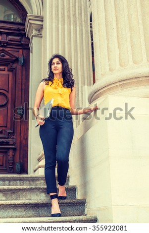 East Indian American college student studying in New York, wearing sleeveless orange shirt, striped pants, high heels, carrying laptop computer, walking down stairs. Instagram filtered look.  - stock photo