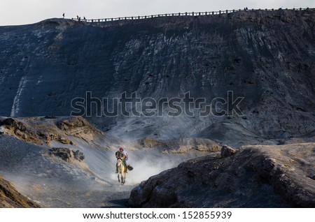 EAST JAVA,INDONESIA-MAY 05 : Tourists ride the horse at Mount Bromo, The active volcano is one of the most visited tourist attractions on May 05,2013 in East Java, Indonesia.  - stock photo