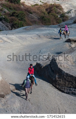 EAST JAVA,INDONESIA-MAY 05 : Tourists ride the horse at Mount Bromo, The active volcano is one of the most visited tourist attractions on May 05,2013 in East Java, Indonesia - stock photo
