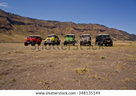 EAST JAVA, INDONESIA-NOV 21 : Colourful jeeps at Blok savana in sunrise light in Bromo Tengger Semeru National Park on November 21, 2015 in East Java , Indonesia. - stock photo