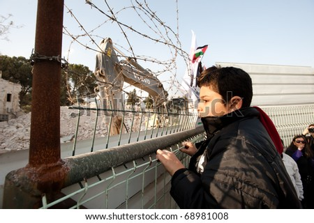 EAST JERUSALEM - JANUARY 14:  A Palestinian boy climbs a fence during a protest at the site of the demolition of a building to make way for a Jewish-only settlement in East Jerusalem on Jan 14, 2011. - stock photo