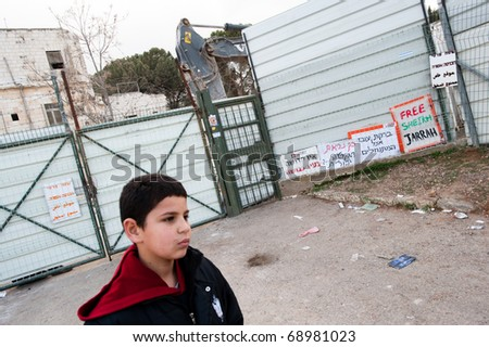 EAST JERUSALEM - JANUARY 14: A Palestinian boy from East Jerusalem stands near protest signs at a building demolition site making way for a Jewish-only settlement on Jan. 14, 2011. - stock photo