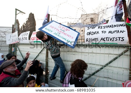 EAST JERUSALEM - JANUARY 14: A Palestinian boy places protest signs atop the fence where a building was demolished in order to construct a Jewish-only settlement in East Jerusalem on Jan 14, 2011 - stock photo