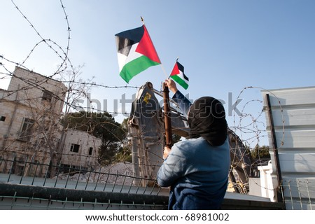 EAST JERUSALEM - JANUARY 14: An Arab woman puts Palestinian flags on the fence while protesting the demolition of a building to construct a Jewish-only settlement in East Jerusalem on Jan 14, 2011. - stock photo
