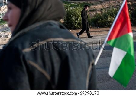 EAST JERUSALEM - JANUARY 28: An orthodox Jewish man walks by as a Palestinian activist protests Jewish settlements in the Sheikh Jarrah neighborhood of East Jerusalem on Jan. 28, 2011. - stock photo