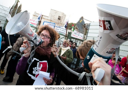 EAST JERUSALEM - JANUARY 14:  Israeli activists lead a demonstration against plans to construct a Jewish-only settlement on the site of the demolished Shepherd Hotel in East Jerusalem on Jan. 14, 2011 - stock photo