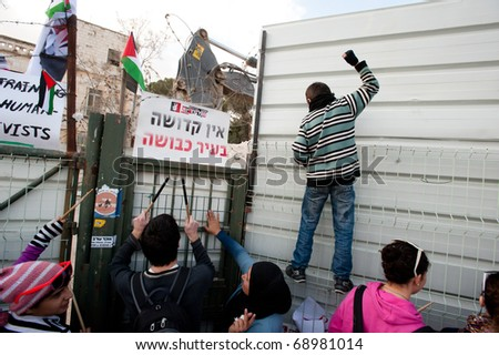 EAST JERUSALEM - JANUARY 14: Palestinian and Israeli activists pound on the fence in protest where a building demolished to make way for Jewish-only settlements in East Jerusalem on Jan 14, 2011. - stock photo