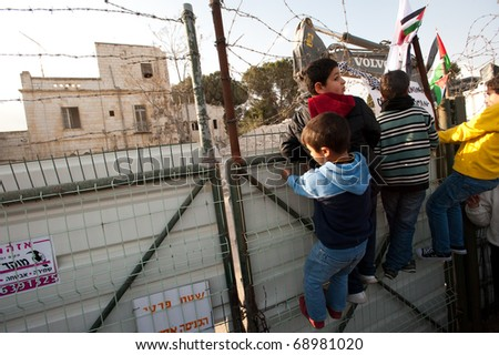 EAST JERUSALEM - JANUARY 14:  Palestinian boys climb a fence during a protest at the site of the demolition of a building to make way for a Jewish-only settlement in East Jerusalem on Jan 14, 2011. - stock photo