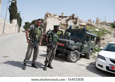 EAST JERUSALEM, OCCUPIED PALESTINIAN TERRITORIES - APRIL 17: Unidentified soldiers of the Israeli Border Police stand in front of a demolished Palestinian house on April 17, 2011 in East Jerusalem.