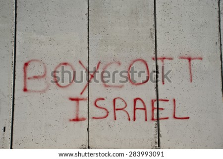 "EAST JERUSALEM, OCCUPIED PALESTINIAN TERRITORIES - MARCH 26: Graffiti on the Israeli separation wall dividing the East Jerusalem neighborhood of Abu Dis reads, ""Boycott Israel"", March 26, 2012. - stock photo"