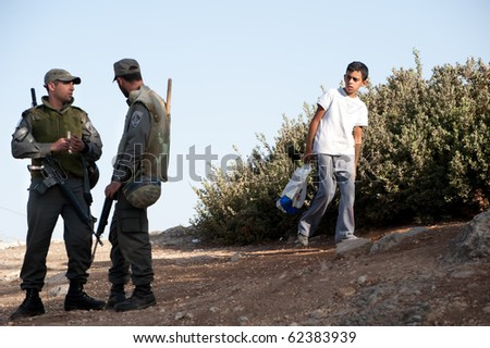 EAST JERUSALEM - OCTOBER 1: A Palestinian boy walks near Israeli police guarding Israeli settlements in the Arab East Jerusalem neighborhood of Sheikh Jarrah on Oct. 1, 2010.