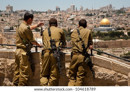 EAST JERUSALEM, PALESTINIAN TERRITORIES - JUNE 2: Israeli soldiers look at Jerusalem's Old City, June 2, 2012. Annexed by Israel, internationally it is still considered occupied Palestinian territory. - stock photo