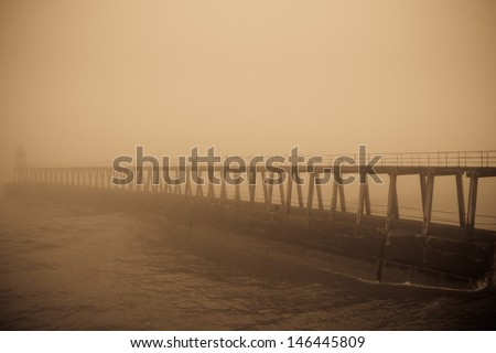 East pier, Whitby, partially obscured by thick fog. - stock photo