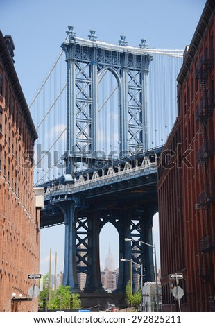 east tower of manhattan bridge framed with old building in brooklyn