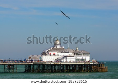 EASTBOURNE, EAST SUSSEX/UK - AUGUST 11 : Avro Lancaster and Spitfire MK1 flying over Eastbourne Pier in Eastbourne on August 11. Unidentified people. - stock photo