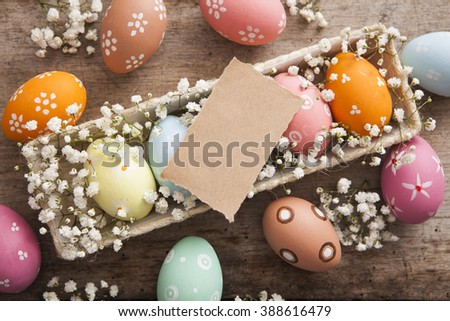 Easter background. Beautiful colorful eggs with spring flowers over wooden brown background - stock photo