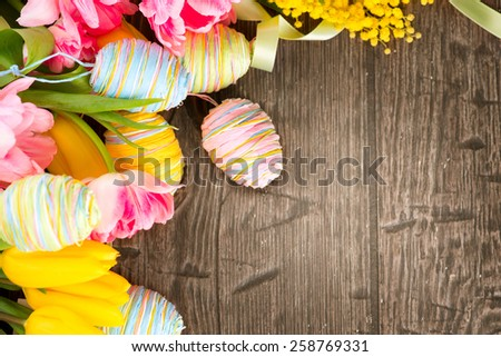 Easter Background. Beautiful Easter holiday backdrop frame decorated with colourful eggs and tulip flowers. Springtime. Invitation card design with space for your text - stock photo