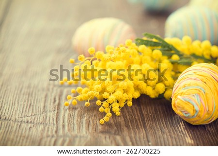 Easter Background. Beautiful Easter holiday border decorated with colourful eggs and mimosa flowers. Springtime. Invitation card design with space for your text - stock photo