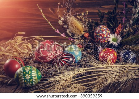 Easter background. colored Easter eggs in the nest, composition of dried flowers, plants and ears of wheat. on wooden background. Easter theme. Happy Easter. instagram toning and soft light effect - stock photo