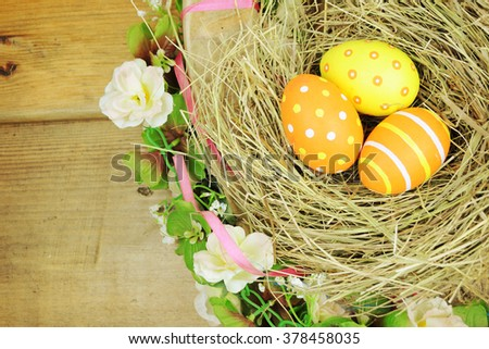 Easter background. Easter eggs in nest on rustic wooden planks