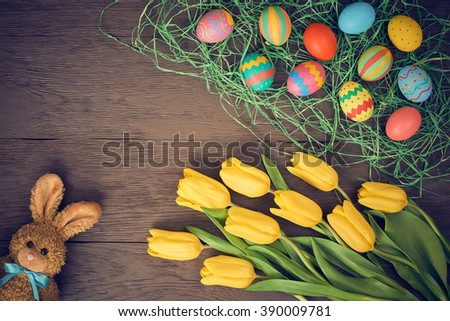 Easter background, eggs, rabbit and yellow tulips. Hand painted decorated eggs on straw, happy bunny handmade and spring flowers, wood, copy space.Still life, top view.Unusual creative greeting card  - stock photo