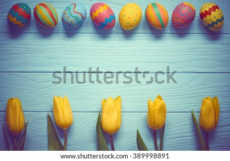 Easter background, eggs with yellow tulips. Hand painted multicolored decorated eggs and spring flowers on blue wood, copy space.  Still life, top view. Unusual creative holiday greeting card  - stock photo