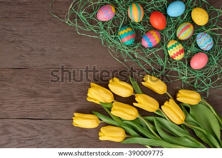 Easter background, eggs with yellow tulips. Hand painted multicolored decorated eggs on straw and spring flowers, wood, copy space.  Still life, top view. Unusual creative holiday greeting card  - stock photo
