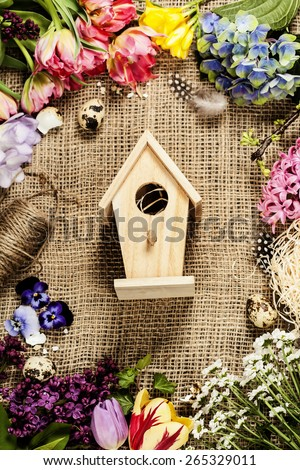 Easter background with bird house, eggs, nest and flowers - stock photo