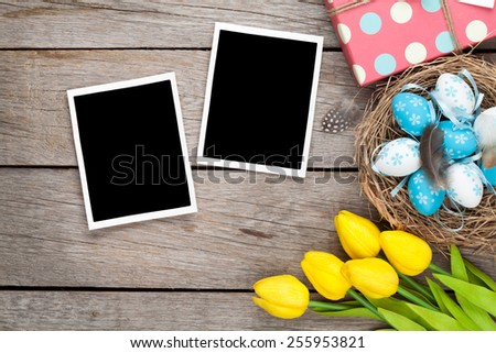 Easter background with blank photo frames, blue and white eggs, yellow tulips and gift box. Top view - stock photo