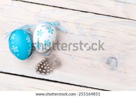 Easter background with blue and white eggs and feather over white wood. Top view with copy space - stock photo