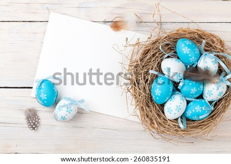 Easter background with blue and white eggs in nest and greeting card over white wood. Top view with copy space  - stock photo