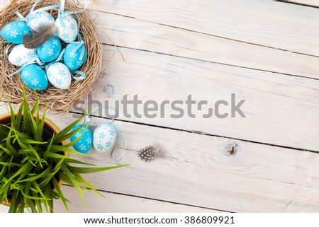 Easter background with blue and white eggs in nest over white wood. Top view with copy space - stock photo