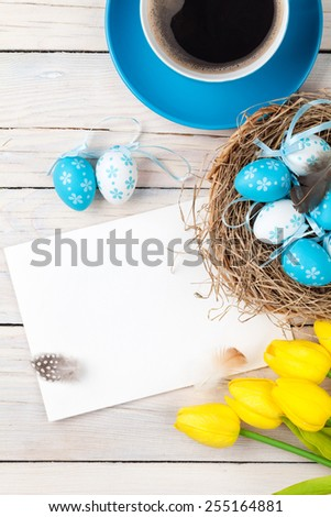 Easter background with blue and white eggs in nest, yellow tulips and greeting card over white wood. Top view with copy space - stock photo