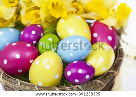Easter background with colorful Easter eggs and a bouquet of yellow daffodils - stock photo