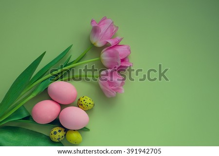Easter background with colorful eggs and pink tulips over light green background. Happy Easter. Easter Holiday flowers bunch with bright eggs. Spring flowers. Top view with copy space. - stock photo
