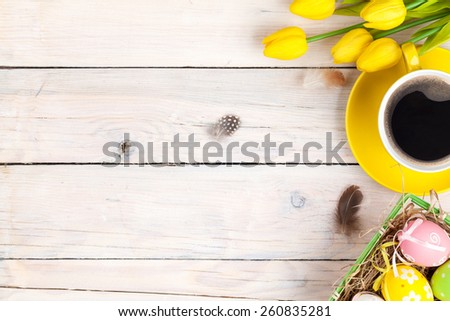 Easter background with colorful eggs and yellow tulips over white wood. Top view with copy space  - stock photo