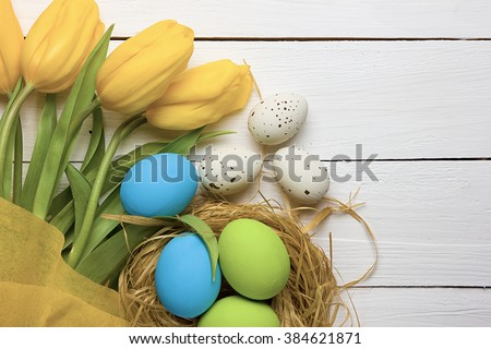 Easter background with colorful eggs in nest and yellow tulips over white wood. Top view with copy space - stock photo