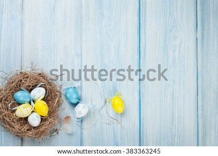 Easter background with eggs in nest over blue wooden table. Top view with copy space - stock photo