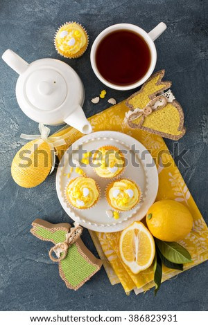 Easter background with lemon cupcakes for Easter brunch with yellow frosting and sprinkles - stock photo