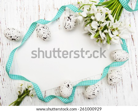 Easter background with snowdrops, eggs and ribbon - stock photo