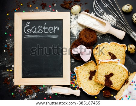 Easter baking background festive cake with chocolate bunny inside. Creative holiday recipe on black background top view with space for text - stock photo