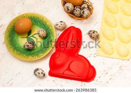 Easter baking Easter bunny template for chocolate eggs and quail eggs in a basket on a white wooden background. Easter card. - stock photo